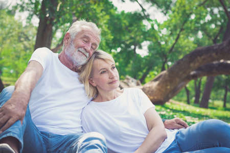 Cheerful couple sitting in the park Imagens