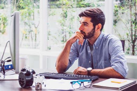 Jeune homme d'affaires barbu travaillant sur un ordinateur portable alors qu'il était assis à son bureau à domicile. Problèmes commerciaux. Banque d'images
