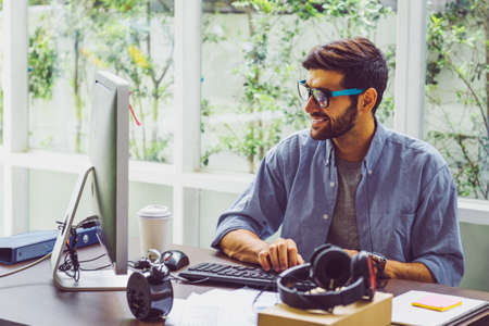 Happy young man, wearing glasses and smiling, as he works on his laptop to get all his business done early in the morning
