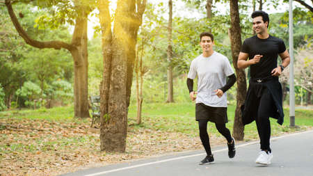 Happy man jogging with friends in the park Stockfoto