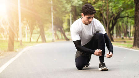 A young runner man sitting and tying the shoelace