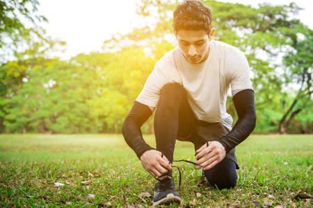 A young runner man sitting and tying the shoelace before jogging