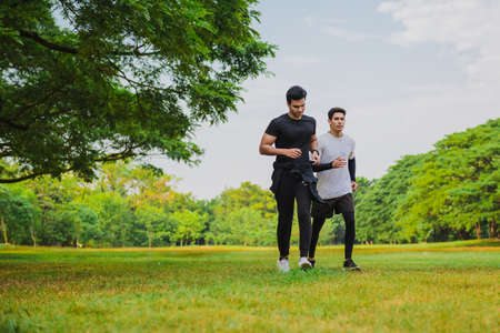 Sportman running in the green park with friend