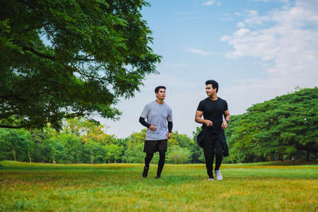 Young man running with his friend in the green park 版權商用圖片