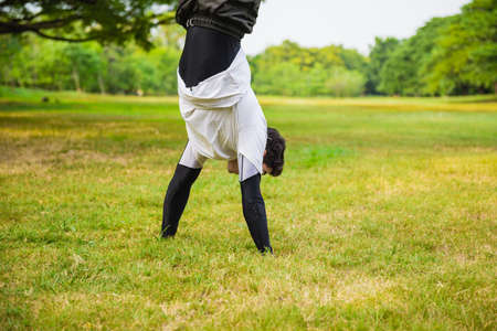 Sportsman doing a handstand on the grass