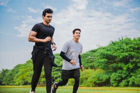 Young man running in the green park with friend