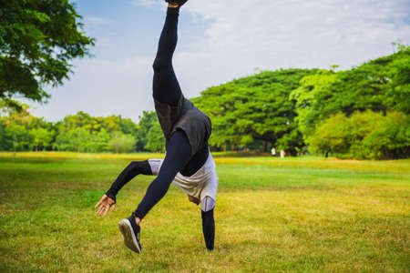 Sportsman doing a handstand on the grass in the park