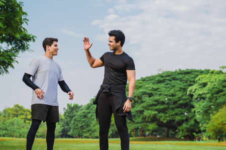 Happy friends giving high five outdoors in a park after exercise