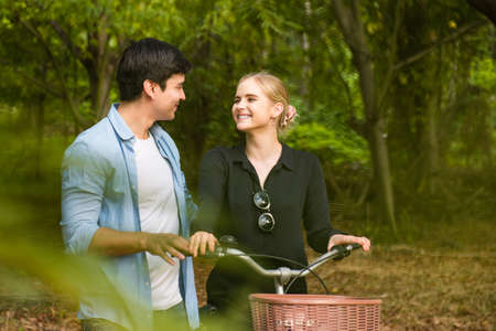 Happy young couple going for a bike ride in the park.