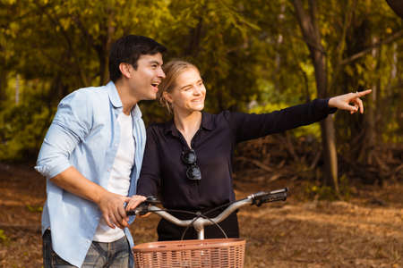 Happy young couple in love and going for a bike ride on a sunny day in the park.