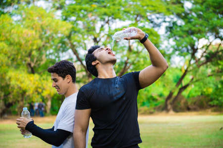 Two young man drinking some water from a bottle Standard-Bild