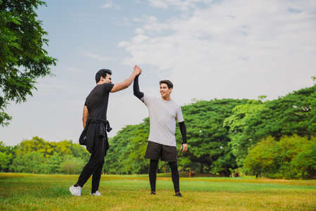 Two men giving high five in the park after breaking a new time record
