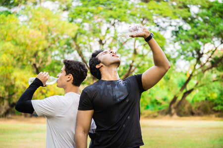 Two men drinking water from bottle after fitness sport exercise.