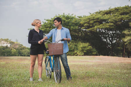 Lovely couple walking through the park with bicycle Stockfoto