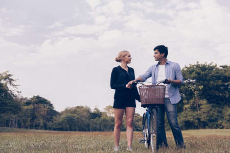 Happy young couple going for a bike ride on a sunny day in the park. Banque d'images