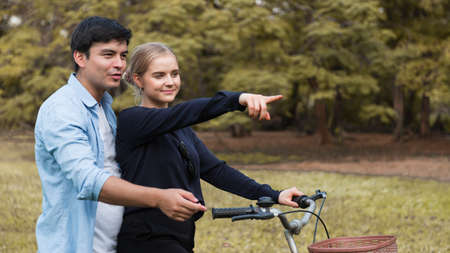 Young couple with bicycle walking in park on sunny autumn day. Stockfoto