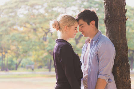 Young couple in love, hugging under the tree in the park