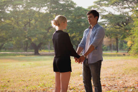 Couple in love walking in the autumn park holding hands looking in the sunset