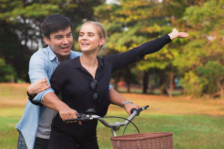 Happy young couple walking their bike along happily talking in park Stockfoto