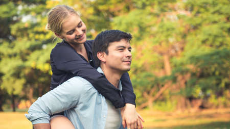 Pretty girl is riding on back of handsome guy in park.
