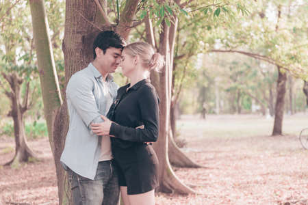 Young beautiful couple kissing and embrace under the tree Stockfoto