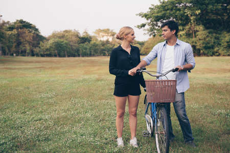 Young couple walking through the park with bicycle