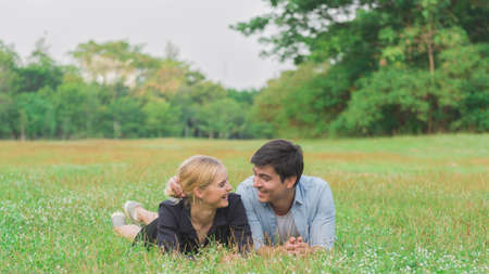 Happy smiling couple in love relaxing on green grass outdoor in park Stockfoto