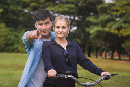 couple together enjoying romantic walk with bicycle in park