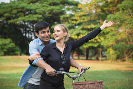 Beautiful young couple walking their bike along happily talking in park