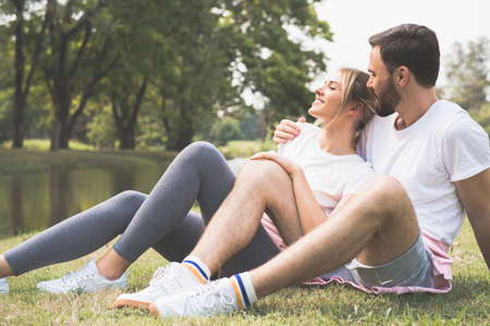 Young couple is hugging and sitting close in the forest Stockfoto