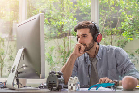 Young man working and concentrate on monitor while sitting at his working place in office while listening music Stockfoto