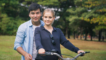 active couple together enjoying romantic walk with bicycle in park Standard-Bild