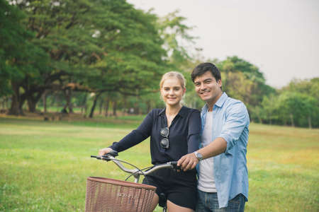 Lovely couple walking through the park with bicycle Standard-Bild