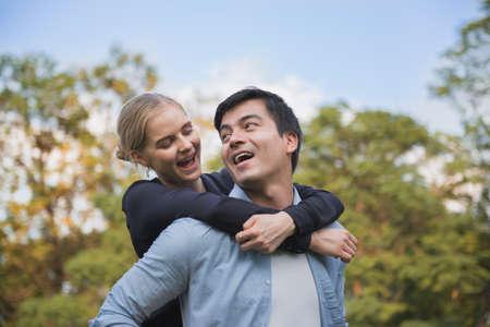 Couple in love. Boyfriend carrying his girlfriend on piggyback. Standard-Bild