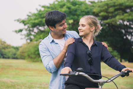 Young couple riding a bicycle in the park. Standard-Bild