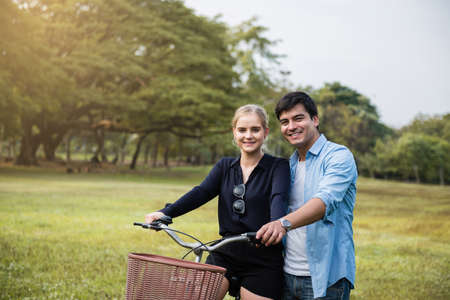 Happy young couple riding a bicycle in the park.