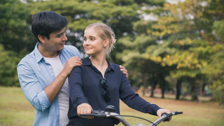 happy couple riding a bicycle in the park.