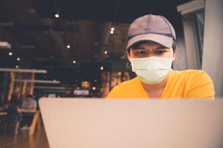 A man in yellow shirt and medical mask using laptop and smartphone while sitting in coffeeshop Standard-Bild