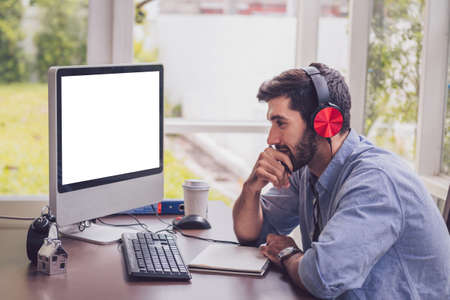 Confident young man working and concentrate on monitor while sitting at his working place in office Standard-Bild