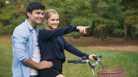 Caucasian young couples walking with a bicycle in the natural park