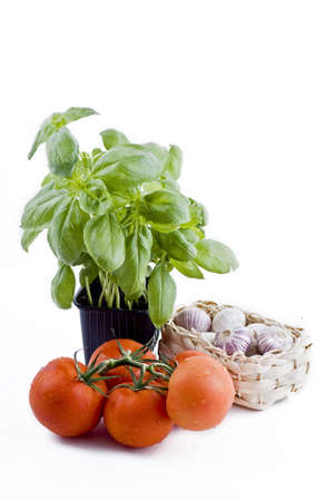 Isolated fresh vegetables - basil in pot, bunch of tomatoes and garlic basket photo
