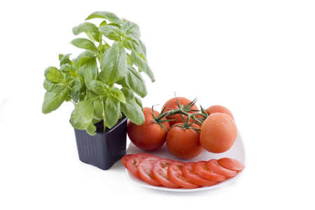 Fresh pot of the basil and plate with bunch of tomatos and sliced tomatos photo