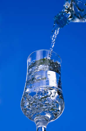 Pouring glass of water on the blue sky background photo