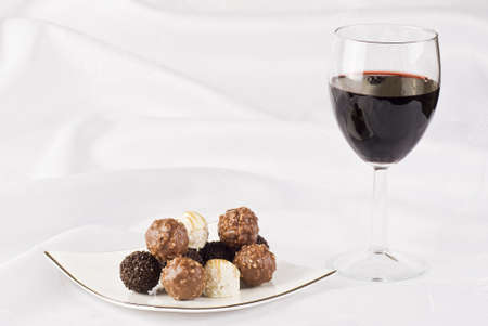 chocolate treats: Red wine and plate of chocolate on the table cloth Stock Photo