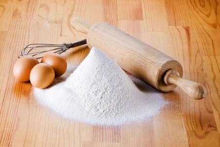 batidora: Harina con huevos, rodillo y batidora en la mesa de madera