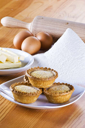 Freshly made apple pies on the table with flour eggs and butter photo