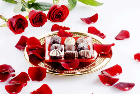 Gold plate of luxury chocolates with red roses photo