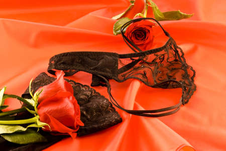 Black strings and stockings with red roses on red background photo