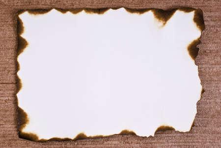 papel quemado: Papel quemado sobre fondo marr�n