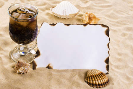 marauder: Burned paper on the sand with shells and ice cold drink Stock Photo